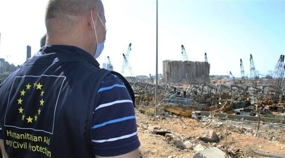 أحد العاملين في الاتحاد الأوروبي إلى جانب مرفأ بيروت المدمر (أرشيف)