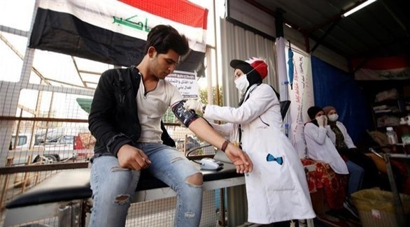 عاملة في القطاع الصحي تسحب عينة دم من شاب عراقي (أرشيف)