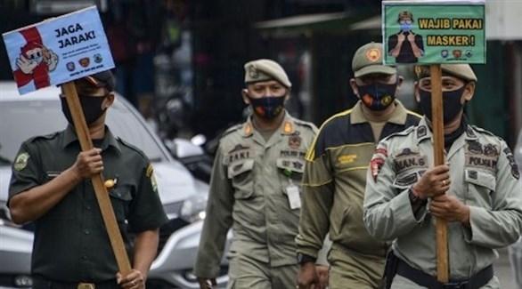 عناصر من الأمن الإندونيسي يرفعون لافتات تدعو السكان لارتداء الكمامات (أ ف ب)