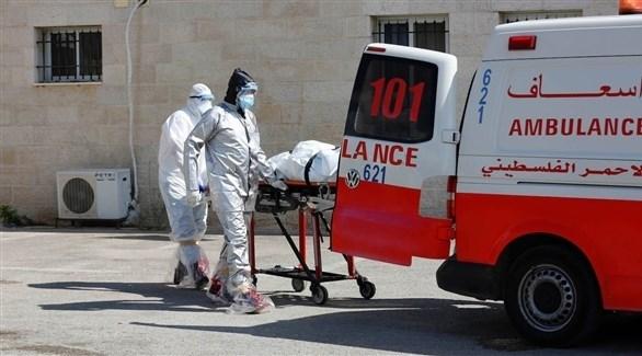 مسعفان فلسطينيان ينقلان جثة أحد ضحايا كورونا إلى سيارة إسعاف (أرشيف)