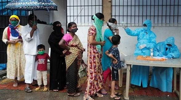 عاملان في قطاع الصحة الهندي يفحصان حرارة مراجعات في مركز صحي (أرشيف)