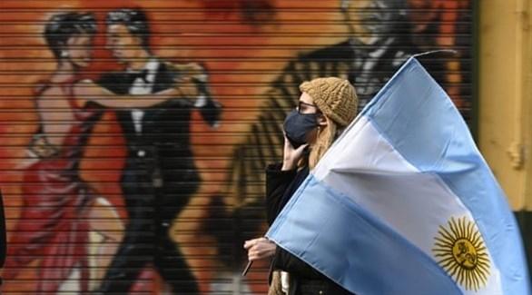 امرأة ترتدي كمامة وتحمل العلم الأرجنتيني (أرشيف / غيتي)