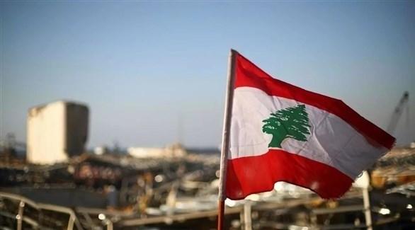 العلم اللبناني وبان خلفه مرفأ بيروت المدمر (أرشيف)