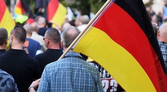شخص يحمل العلم الألماني أثناء مشاركته في تظاهرة (أرشيف)
