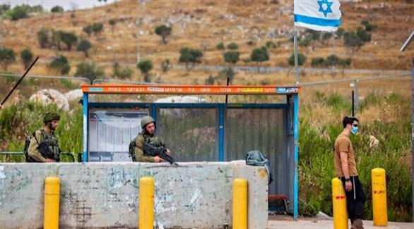 جنديان إسرائيليان في محطة حافلة عند مفترق تبواح (تايمز أوف إسرائيل)
