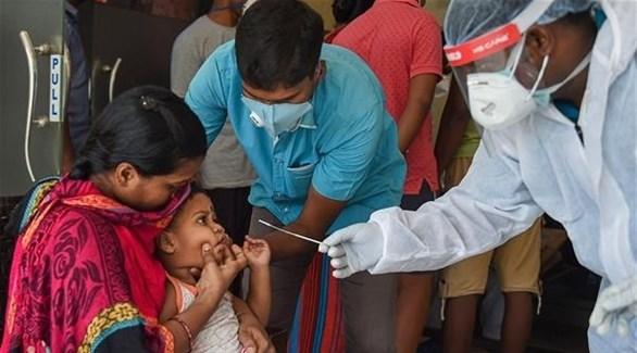 عامل في القطاع الصحي يستعد لأخذ عينة بيولوجية من طفلة هندية لكشف كورونا (أرشيف)
