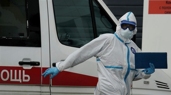 عامل في القطاع الصحي الروسي أمام سيارة إسعاف (أرشيف)