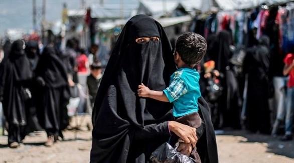 سيدة تحمل طفلها في مخيم الهول بسوريا (أرشيف)