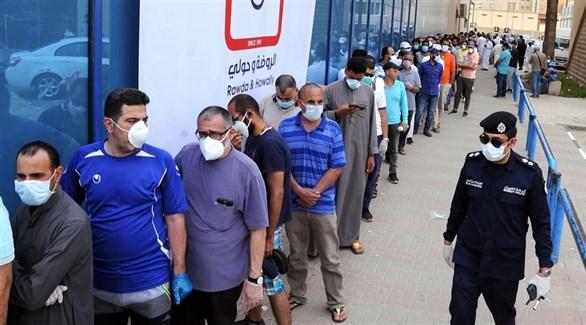 شرطي كويتي إلى جانب طابور من المراجعين أمام مركز صحي في حولي (أرشيف)