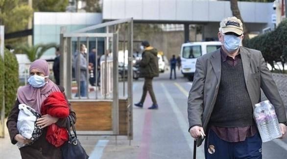 رجل وامرأة يرتديان الكمامة الصحية خوفاً من كورونا (أرشيف)
