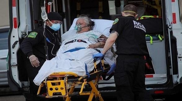مسعفان أمريكيان ينقلان مصابة بكورونا إلى سيارة إسعاف (أرشيف)