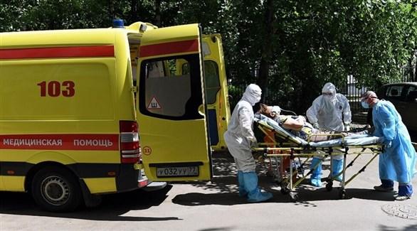 مسعفون روس ينقلون مصابة بكورونا إلى سيارة إسعاف (أرشيف)