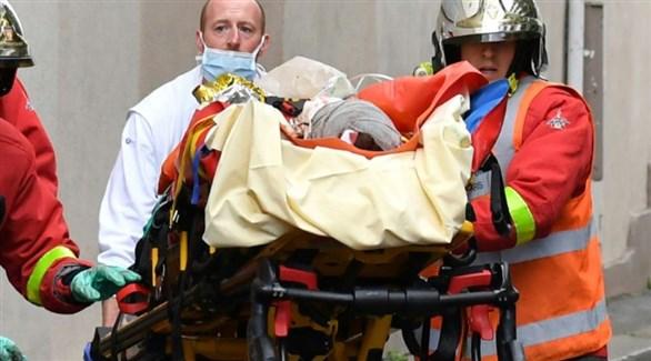 مسعف وعنصرين من الحماية المدنية الفرنسية يُجليان مصاباً في الهجوم (أ ف ب)