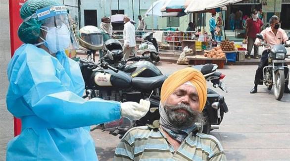 عاملة في القطاع الصحي تسحب عينة بيولوجية من مراجع هندي (أ رشيف)
