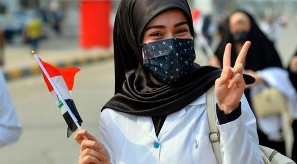 طالبة ترتدي كمامة وتحمل العلم العراقي خلال تظاهرة في النجف (أرشيف / أ ف ب)
