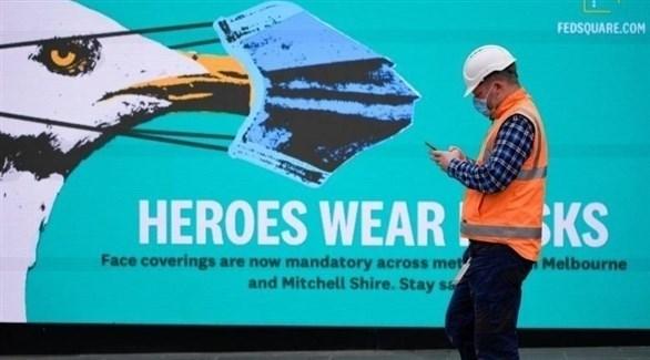 رجل يمر بجانب إعلان يدعو لارتداء الكمامات في استراليا (أرشيف)
