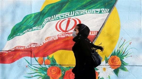 امرأة ترتدي كمامة أثناء مرورها بجانب جدارية للعلم الإيراني (أرشيف)