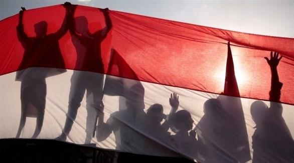 مجموعة من الأشخاص يرفعون العلم اليمني (أرشيف)