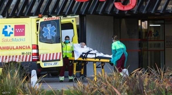 مسعفان إسبانيان ينقلان مصاباً بكورونا إلى سيارة إسعاف (أرشيف)