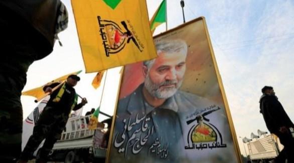 مسلحون من كتائب حزب الله العراق حول صورة لقائد فيلق القدس الإيراني السابق قاسم سليماني (أرشيف)