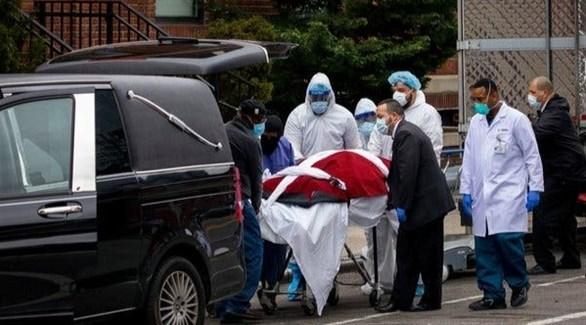عاملون في شركة دفن ينقلون جثة أحد ضحايا كورونا في بروكلين بنيويورك (رويترز)