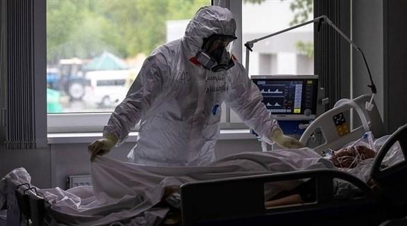 عامل في القطاع الصحي إلى جانب مصابة بكورونا في مستشفى بموسكو (تاس)