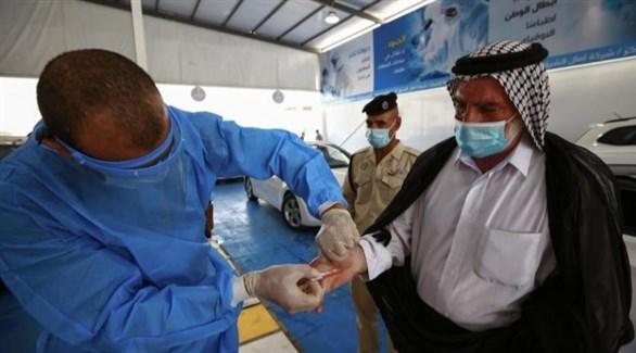 طبيب يأحذ عينة دم من عراقي للكشف عن كورونا (أرشيف)
