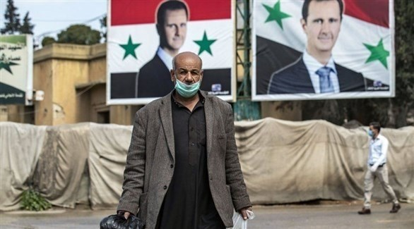 سوري يرتدي كمامة أثناء سيره بالشارع (أرشيف)