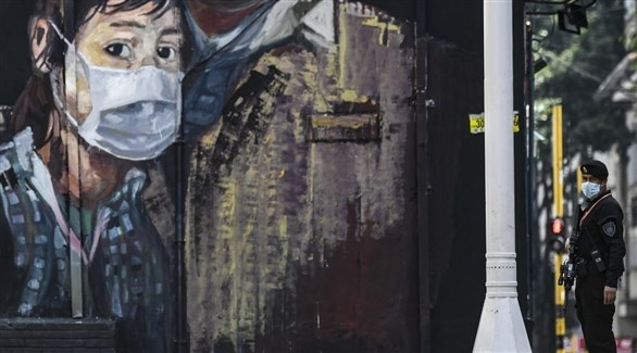 رجل أمن يقف بجانب جدارية تمثل التأمين من كورونا (أرشيف)