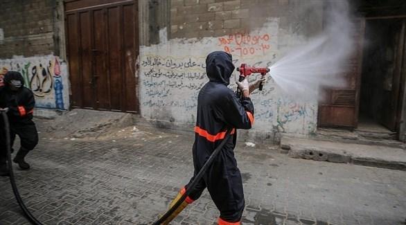 عامل بقطاع الصحة في غزة يعقم حياً للوقاية من كورونا (إ ب أ)