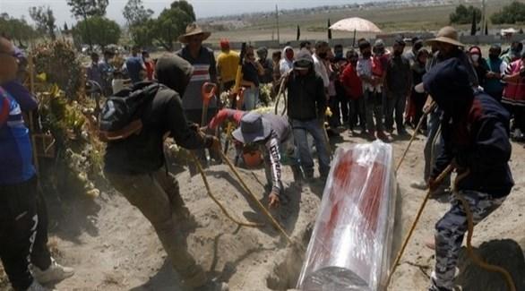 عامل يساهمون في دفن جثث مصابة بفيروس كورونا (أرشيف)