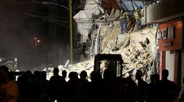 تجمهر للناس بجانب الجرافات وعمال الانقاذ أثناء البحث عن ناجين في بيروت (رويترز)