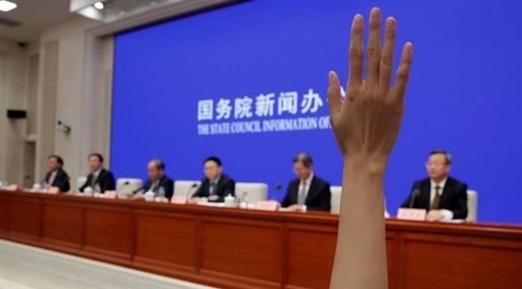 شخص يرفع يده خلال أحد المؤتمرات الصحفية في الصين (أرشيف / رويترز)