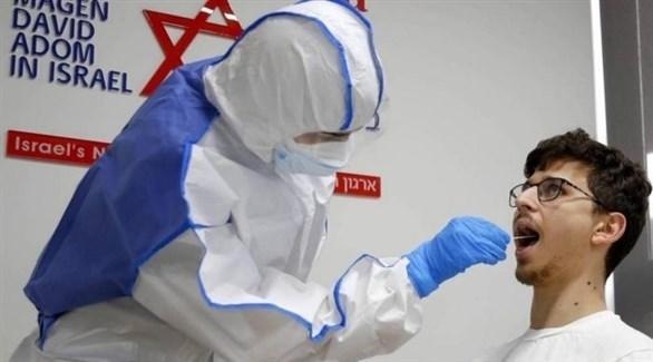 عامل في القطاع الصحي الإسرائيلي يسحب عينة بيولوجية من مُراجع لفحص كورونا (أرشيف)