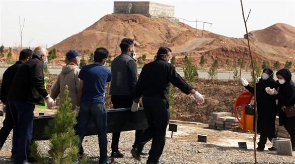 إيرانيون ينقلون نعشاً في مقبرة لدفن أحد ضحايا كورونا (أرشيف)