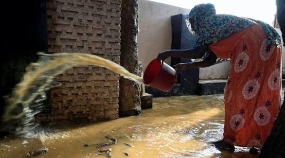 امرأة تحاول التخلص من المياه من داخل منزلها في الخرطوم (رويترز)