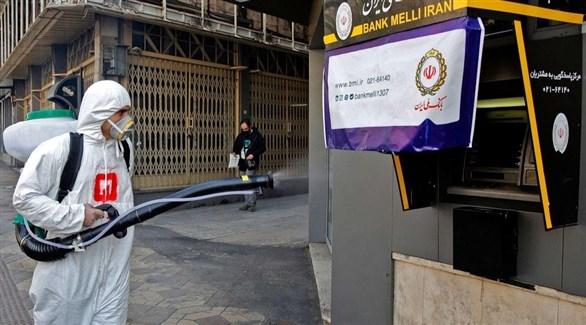 عامل في طهران أثناء تعقيم صراف آلي في أحد الشوارع (أرشيف)