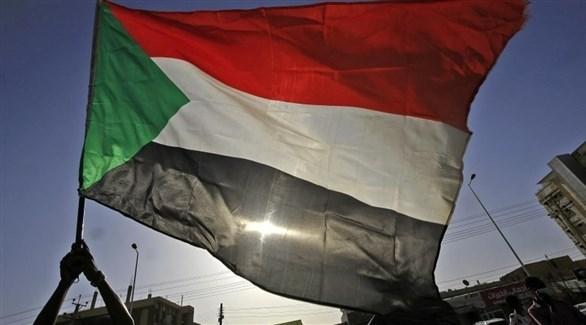 شخص يرفع العلم السوداني (أرشيف)