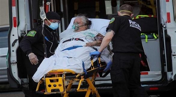 مسعفان ينقلان مصابة بكورونا إلى سيارة إسعاف في أمريكا (أرشيف)