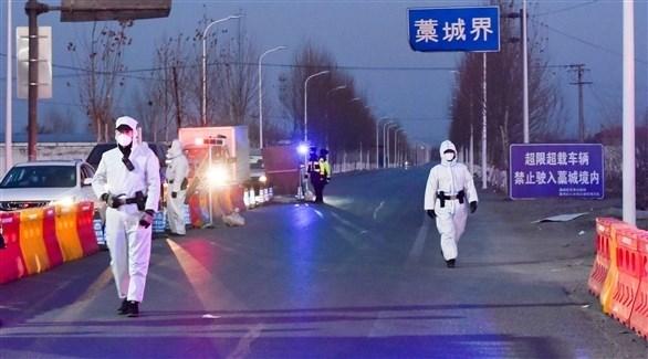عناصر من الأمن الصيني عند مدخل مدينة مُغلقة (رويترز)