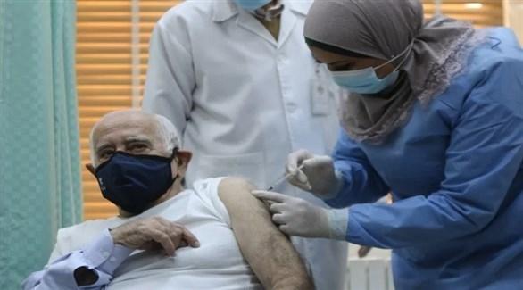 ممرضة تطعم الطبيب الأردني داود حنانيا  باللقاح ضد كورونا (تويتر)