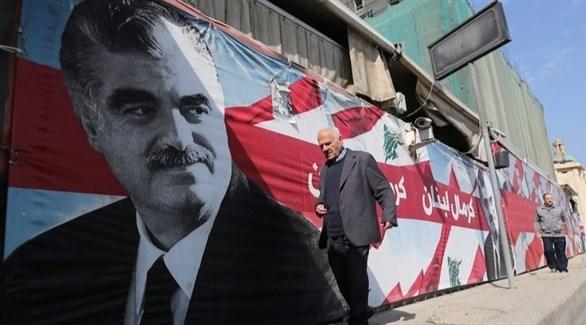 أشخاص يمرون بجانب لافتة تحمل صورة رئيس الحكومة الأسبق رفيق الحريري (أرشيف)