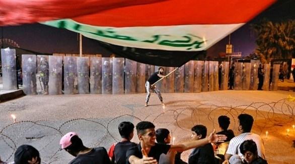 شاب يرفع علماً عراقياً ضخماً في احدى التظاهرات (أرشيف)