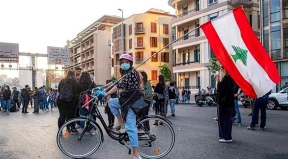 سيدة لبنانية ترفع علم بلادها أثناء تجولها على دراجتها (أرشيف)