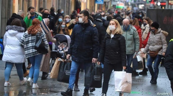 مواطنون ألمان يرتدون الكمامات للوقاية من كورونا (رويترز)