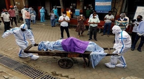 عاملان صحيان هنديان ينقلان جثة أحد ضحايا كورونا (أرشيف)