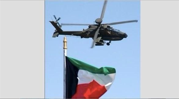طائرة أباتشي تحلق فوق العلم الكويتي (ارشيف)