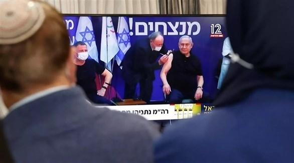 إسرائيليون يتابعون خبر تلقي نتانياهو مطعوم ضد كورونا (أرشيف)