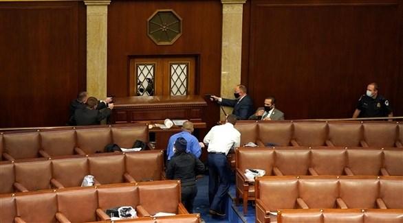 عناصر من أمن الكونغرس يرفعون أسلحتهم أمام باب قاعة مجلس النواب (CNN)