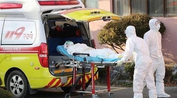 مسعفان ينقلان مصاباً بكورونا إلى سيارة إسعاف في كوريا الجنوبية (أرشيف)